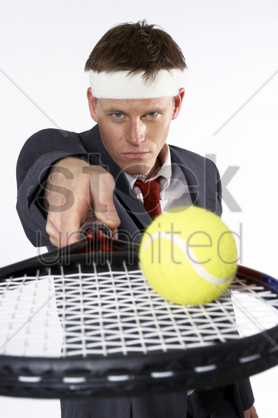 businessman balancing a tennis ball on the racquet stock photo