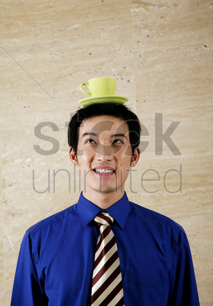 businessman balancing cup on his head stock photo