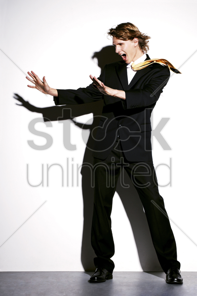 businessman being blown by strong wind stock photo