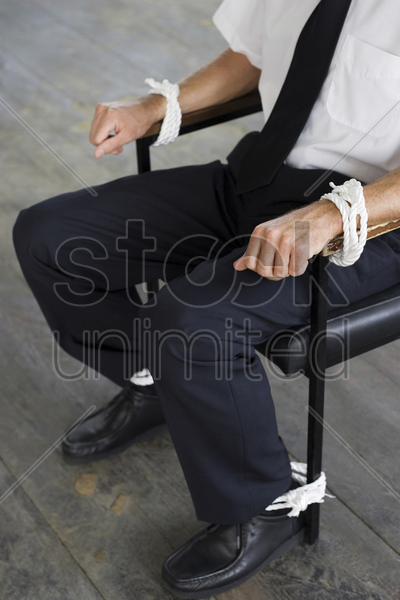 businessman being tied to a chair stock photo