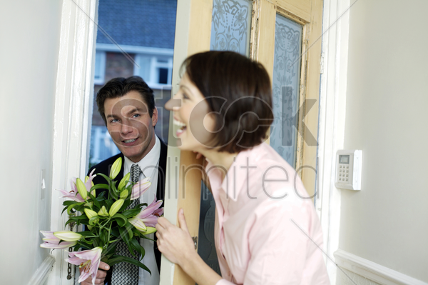 businessman bringing home a bouquet of flowers for his wife stock photo