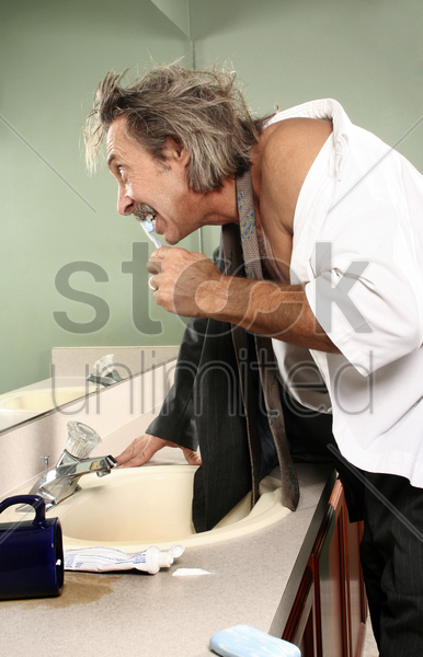 businessman brushing teeth in the toilet stock photo