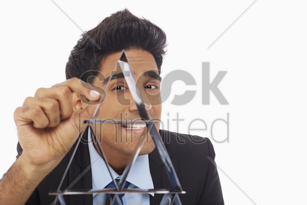 businessman building a pyramid of cards stock photo
