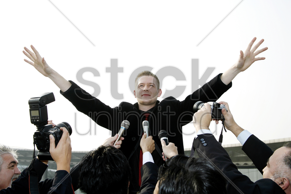 businessman calming down reporters at a press conference stock photo