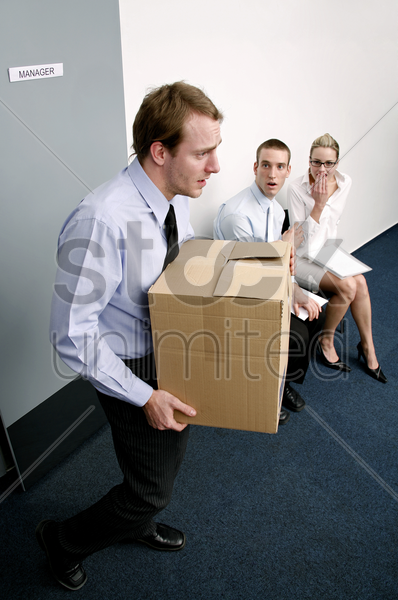 businessman carrying a box of his belongings after being fired stock photo