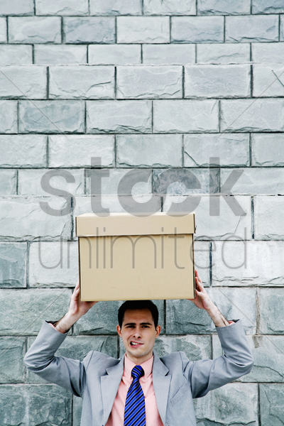 businessman carrying a box on his head stock photo