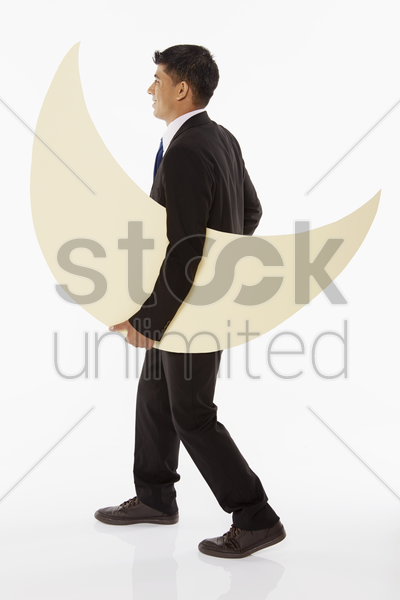 businessman carrying a crescent moon stock photo