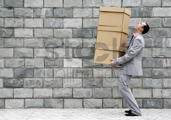 businessman carrying a stack of boxes stock photo