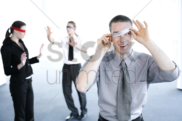 businessman cheating during a blindfolding game stock photo