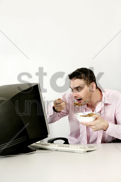 businessman checking his work while eating breakfast cereal stock photo