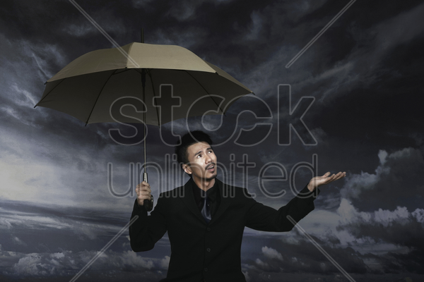 businessman checking on the weather while holding an umbrella stock photo
