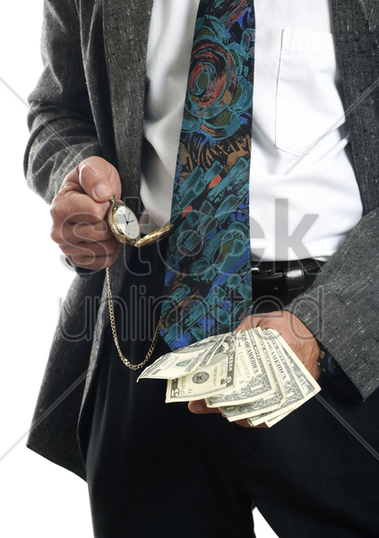 businessman checking the time while holding cash in his hand stock photo
