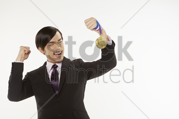 businessman cheering while holding gold medal stock photo