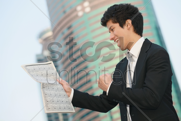 businessman cheering while reading newspaper stock photo