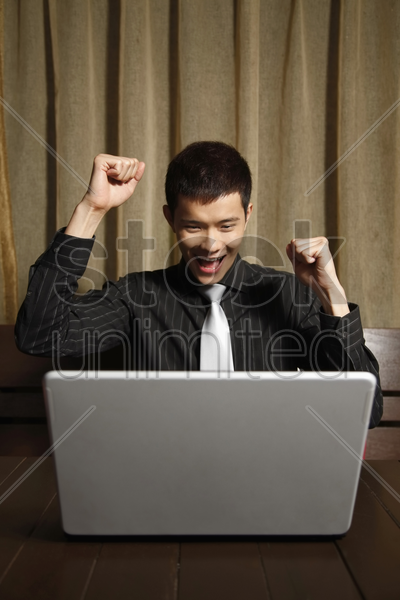 businessman cheering with arms raised stock photo