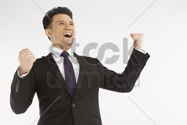businessman cheering with fists in the air stock photo