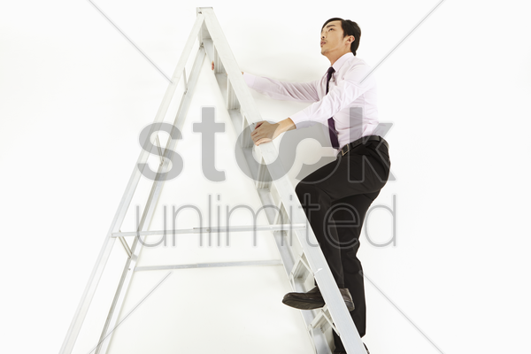 businessman climbing up a ladder stock photo