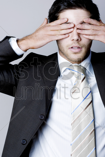 businessman closing his eyes with his hands stock photo