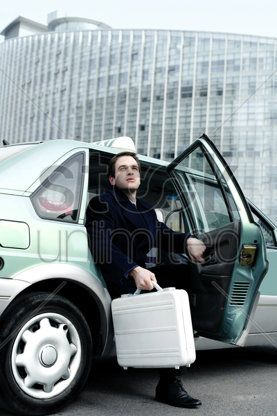 businessman coming out from a taxi stock photo
