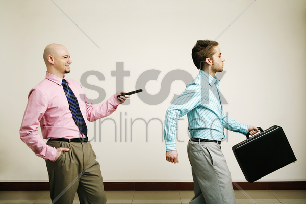 businessman controlling his colleague with a remote control stock photo