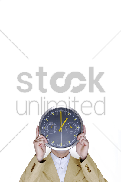 businessman covering his face with a clock stock photo