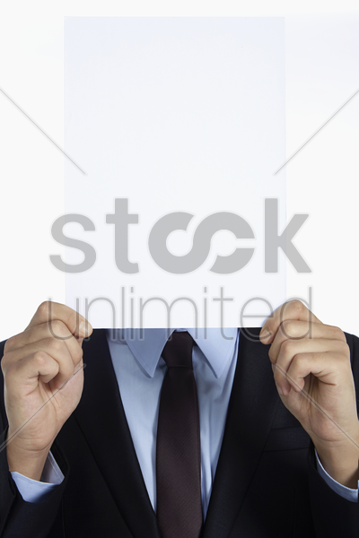businessman covering his face with a piece of paper stock photo