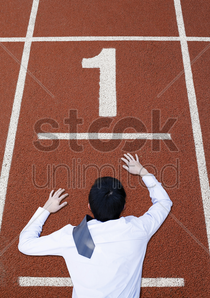 businessman crawling on the running track stock photo
