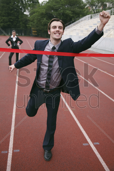 businessman crossing the finishing line stock photo
