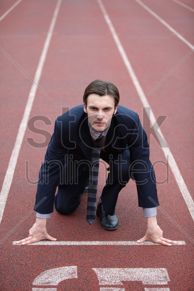 businessman crouching at starting line of track stock photo
