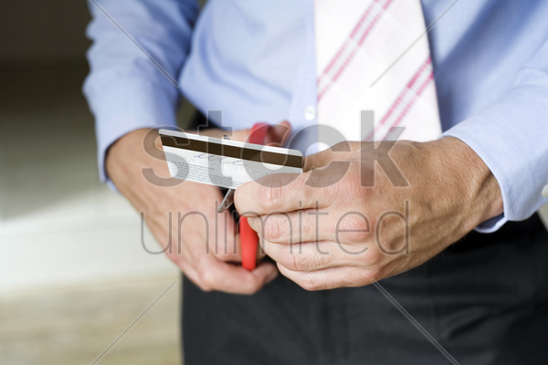 businessman cutting credit card stock photo