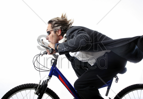 businessman cycling at a fast speed stock photo