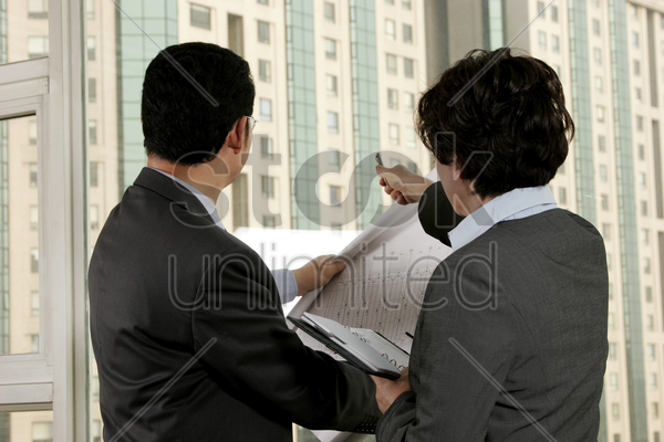 businessman discussing a building plan with his assistant stock photo