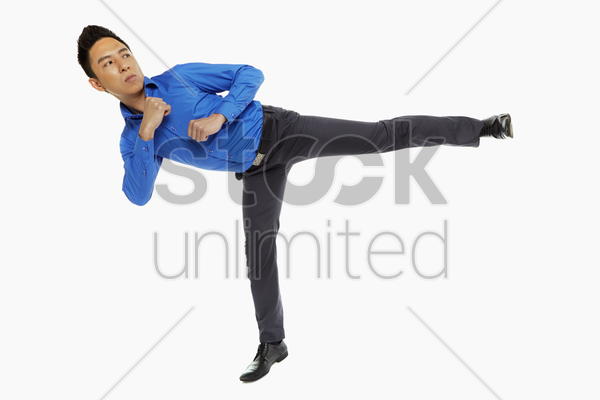 businessman doing a side kick stock photo