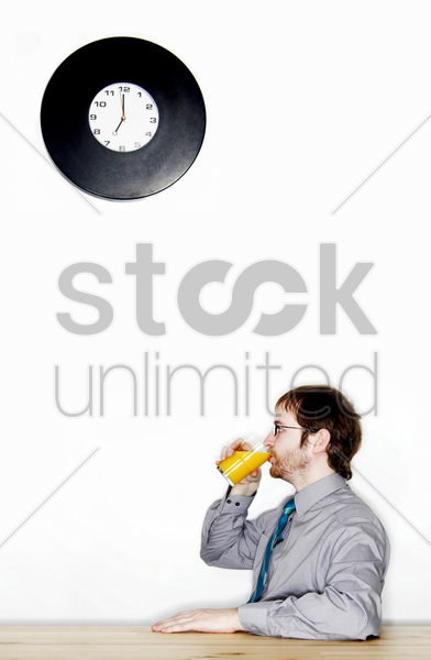 businessman drinking a glass of orange juice stock photo