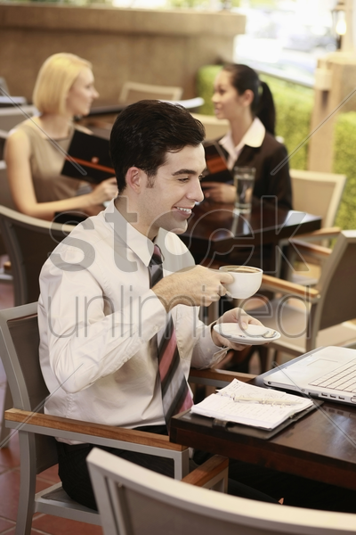businessman drinking coffee while looking at laptop, businesswomen sitting in the background stock photo