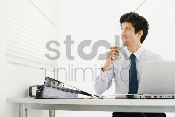 businessman drinking coffee while looking out window blinds stock photo