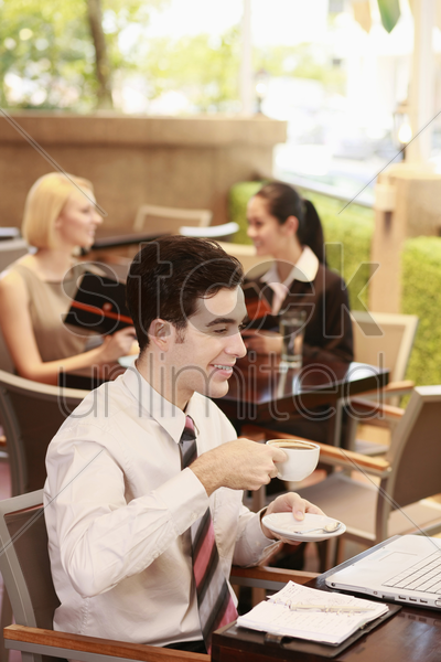 businessman drinking coffee while using laptop stock photo