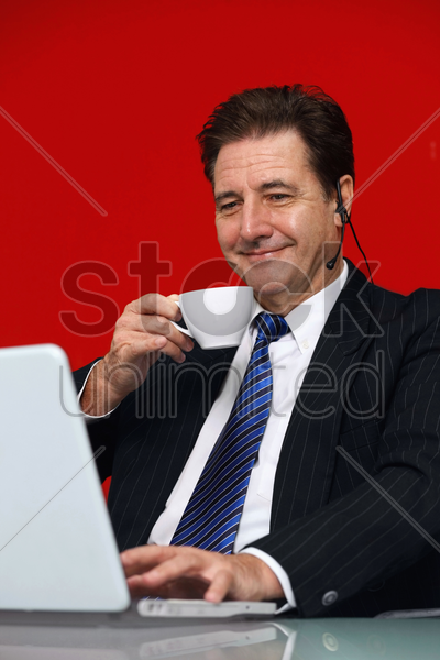 businessman drinking coffee while video conferencing on laptop stock photo