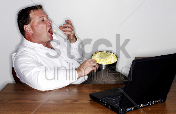 businessman eating popcorn while working on his laptop stock photo