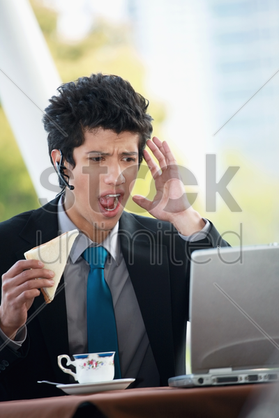 businessman eating sandwich while looking at the laptop stock photo