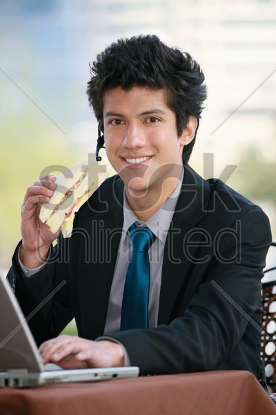 businessman eating sandwich while using laptop stock photo