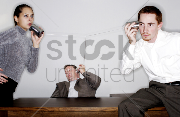 businessman eavesdropping on a tin can phone conversation stock photo