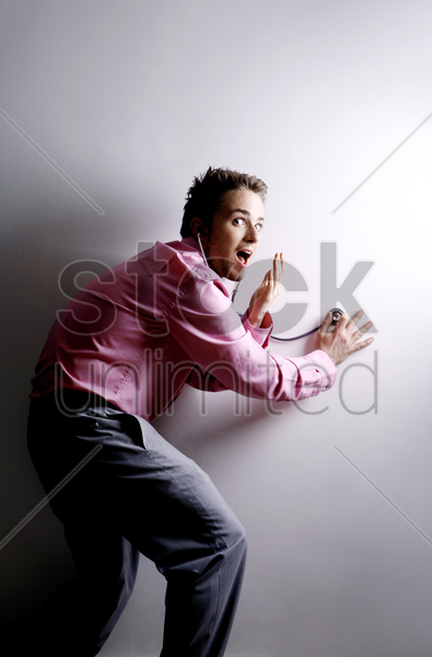 businessman eavesdropping with a stethoscope stock photo