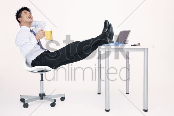 businessman enjoying a glass of beer with his legs on the table stock photo