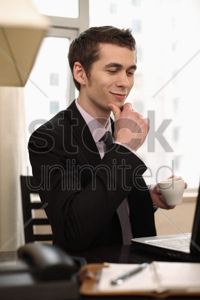 businessman enjoying coffee while using laptop stock photo