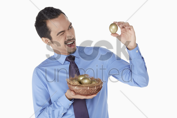 businessman examine a golden egg stock photo