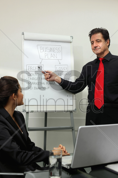 businessman explaining his plan on a board to a partner at the meeting stock photo