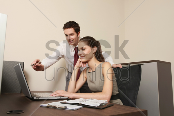 businessman explaining something to businesswoman using laptop stock photo