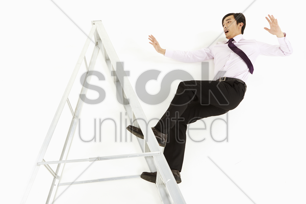 businessman falling off a ladder stock photo
