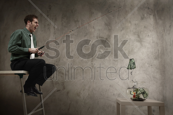 businessman fishing for banknotes from fishbowl stock photo